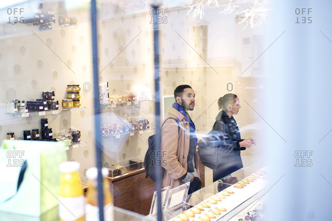 View of couple inside bakery buying treats through a window