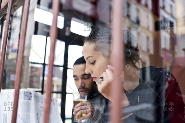 View through window of couple sitting inside a restaurant