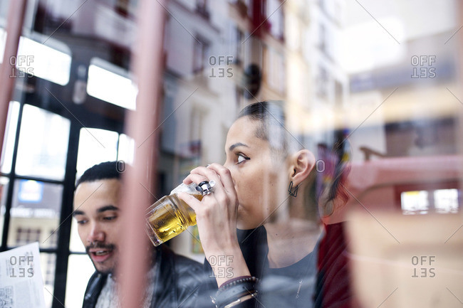 View through window of couple sitting inside a restaurant drinking beer