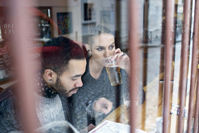 View through window of couple sitting inside a restaurant having a beer
