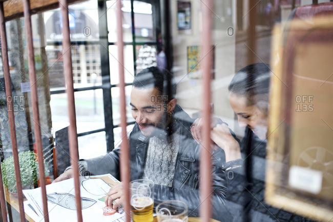 View through window of couple sitting inside a restaurant laughing
