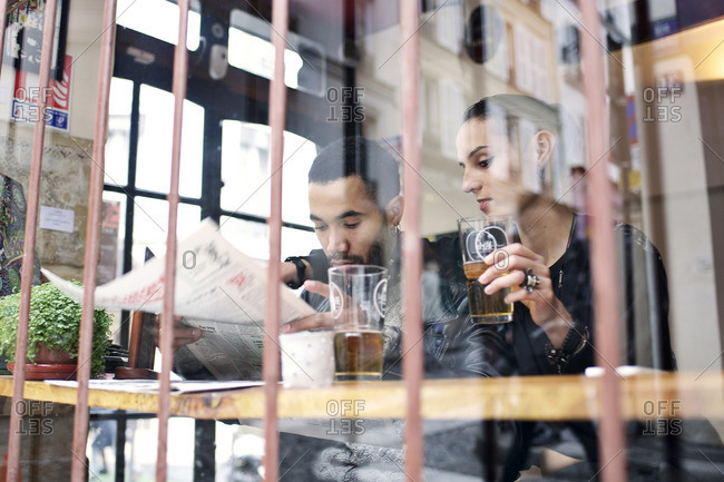 View through window of couple sitting inside a restaurant drinking beer and reading the newspaper