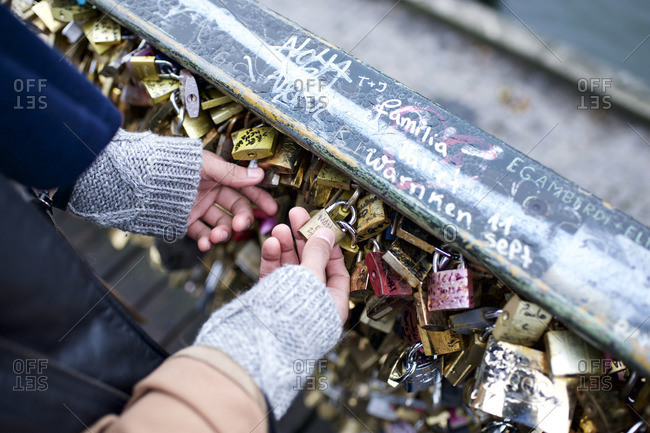 Couple holding padlock on Pont des Arts, Paris, France