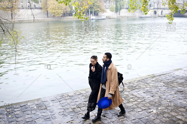 High angle view of couple walking next to Seine River, Paris, France