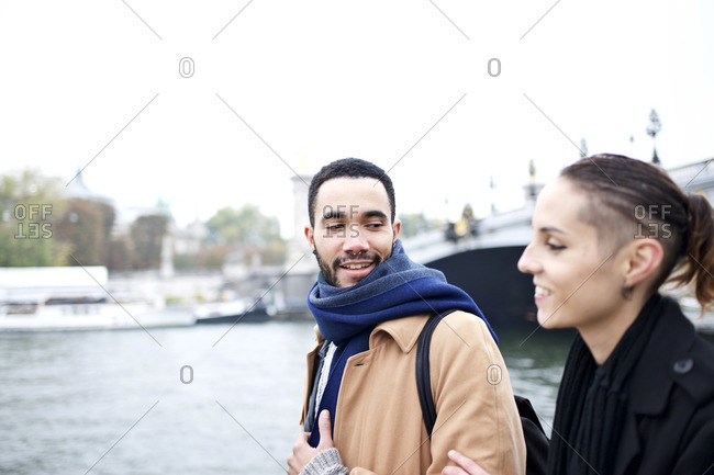 Couple walking next to Seine River, Paris, France