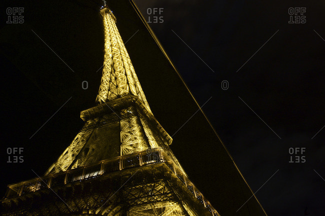 Paris, France - October 16, 2015: Curved reflection of the Eiffel Tower illuminated at night, Paris, France