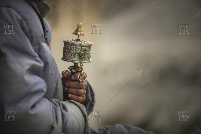 Person holding prayer wheel in rural India