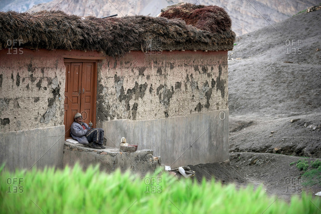 Spiti Valley, India - July 22, 2015: Man on steps of house in remote Himalayas