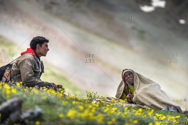 Kumzum Pass, Lahaul & Spiti, India - July 24, 2015: Two men sitting on hillside in Himalayas