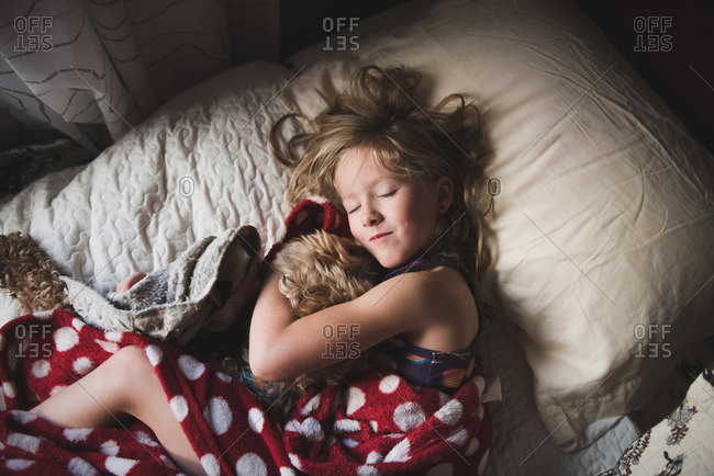 Little girl snuggling with her dog