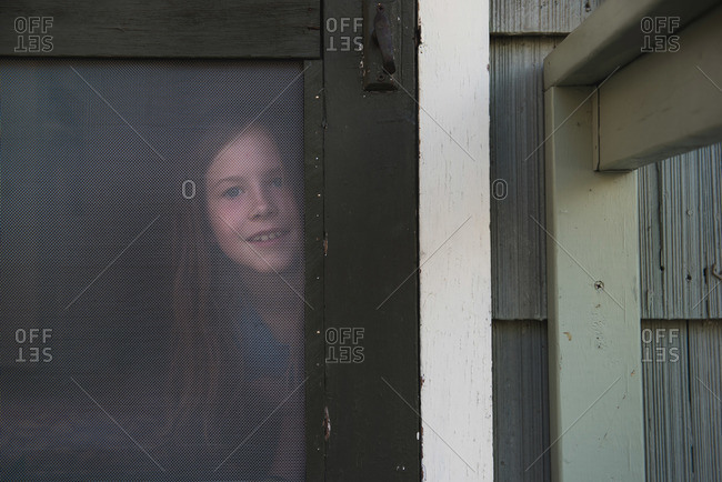 Girl looking through a screen door