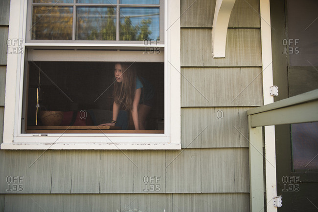 Girl looking out of an open window