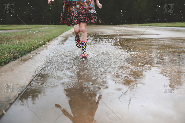 Feet of girl splashing through puddle