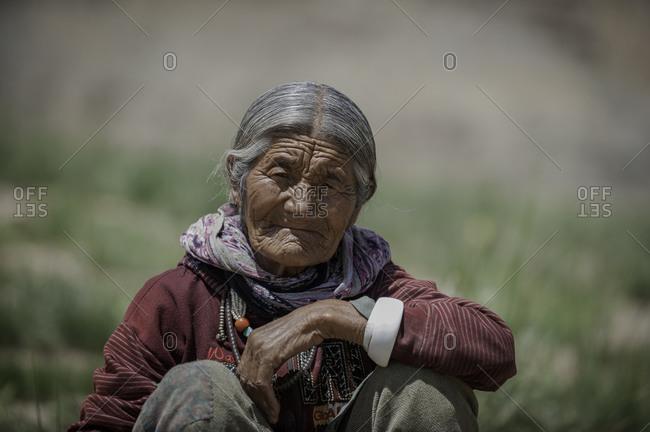 Elderly woman sitting in Indian Himalayas