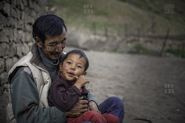 Man and boy sitting by Himalayan house