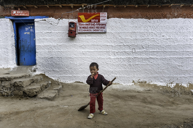 Boy with shovel by remote Himalayan building