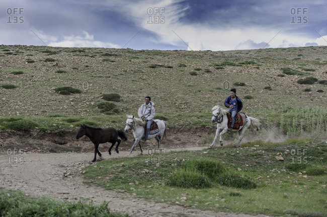 Two men riding horses in remote Himalayas