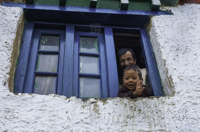 Man and boy looking out window of Himalayan house