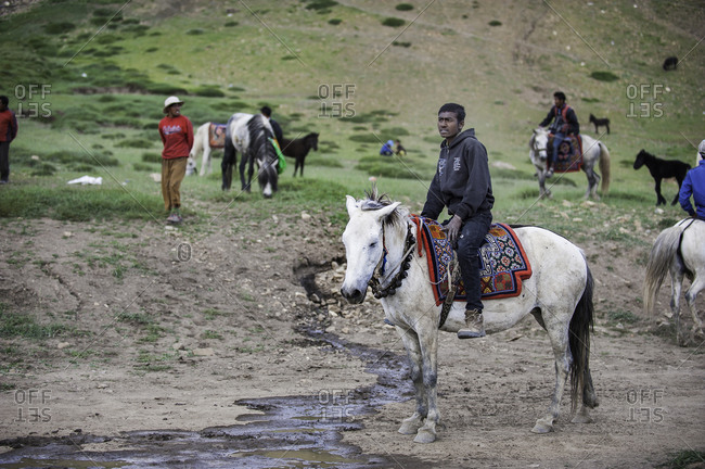 Men gathered with horses in remote Himalayas