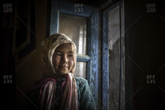 Girl in headscarf by window in Himalayan home