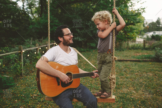 Father and son playing guitar while on a swing