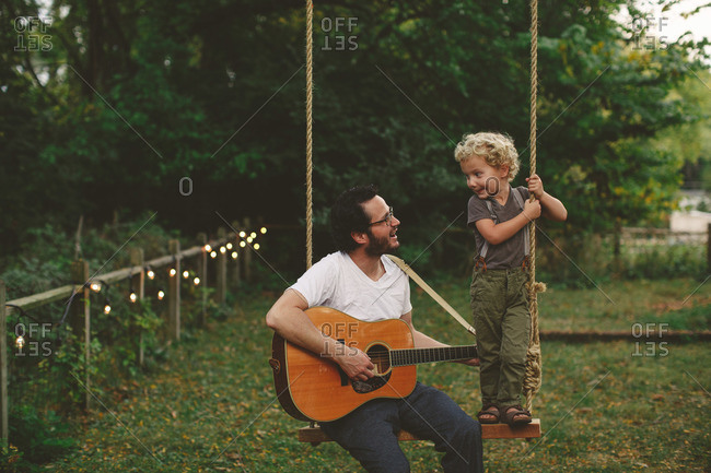 Father playing guitar for his son while on a swing