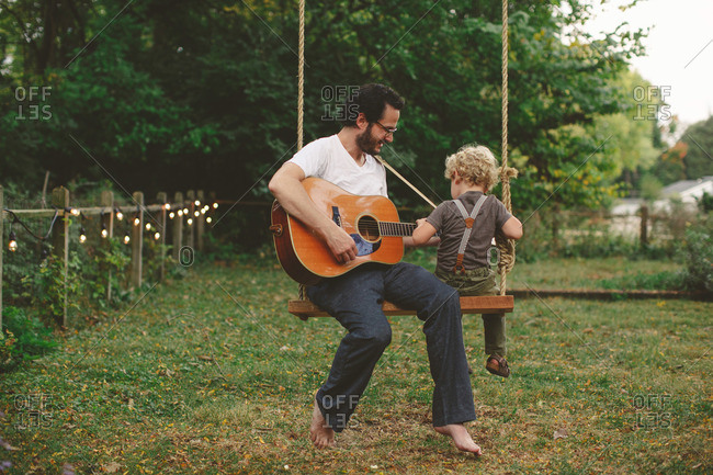 Father and son sitting on a swing with a guitar