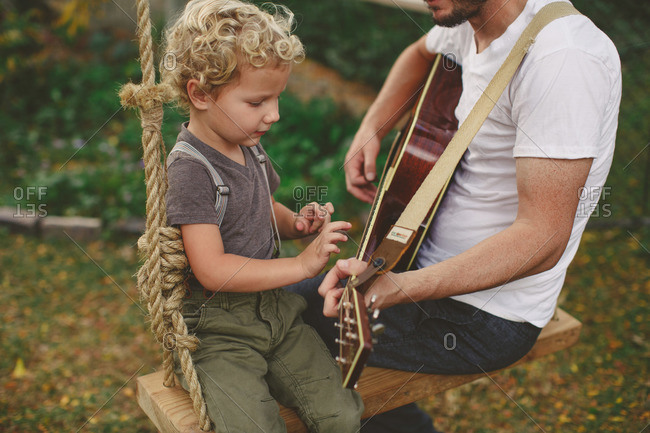 Father and son sitting on a swing playing a guitar