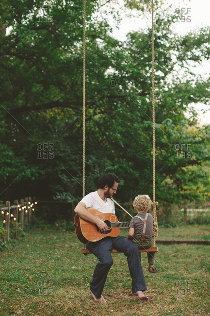 Man playing guitar for his son while sitting on a swing
