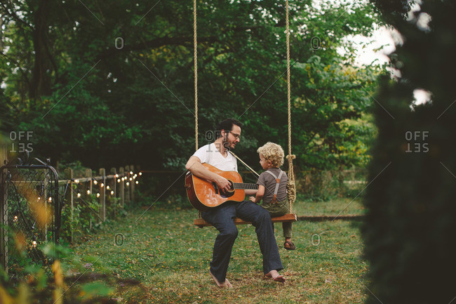 Boy listens to his dad play guitar while on a swing