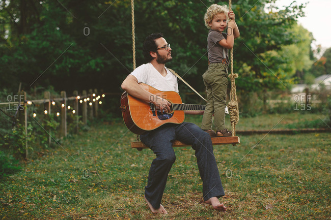 Dad playing guitar for his son while sitting on a swing