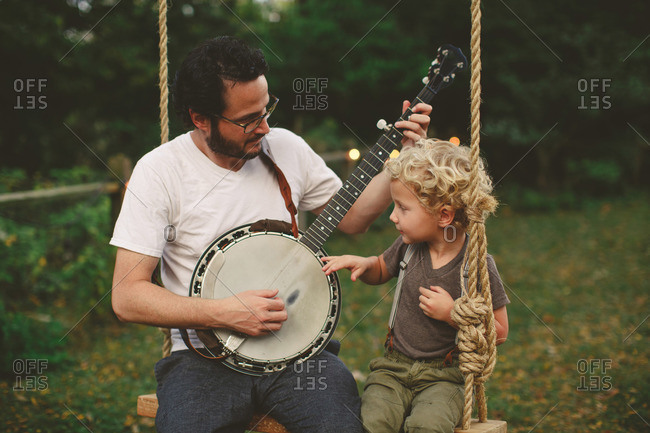 Father and son sitting on a swing playing a banjo
