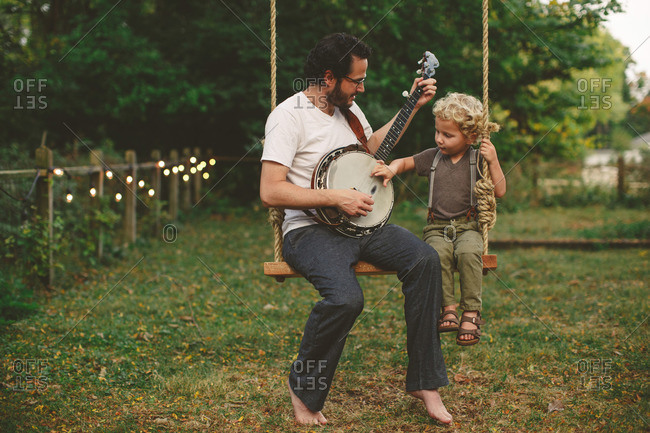 Father and son playing a banjo on a swing