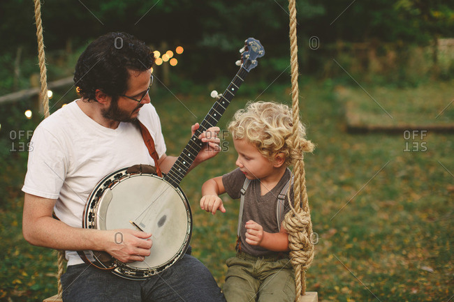 Boy watches his dad play banjo while on a swing
