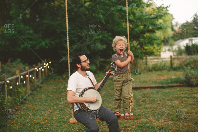 Father and son playing on a swing with a banjo