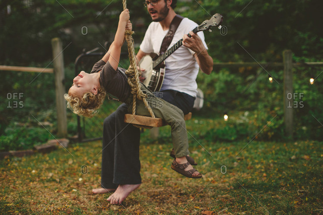 Father playing a banjo for his son while on a swing