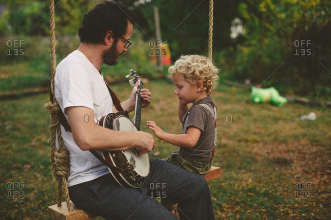 Boy watching his dad play banjo on a swing