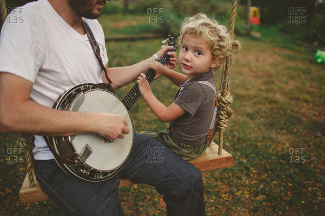 Father and son playing banjo together on a swing