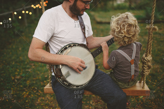Boy and his dad playing banjo together on a swing