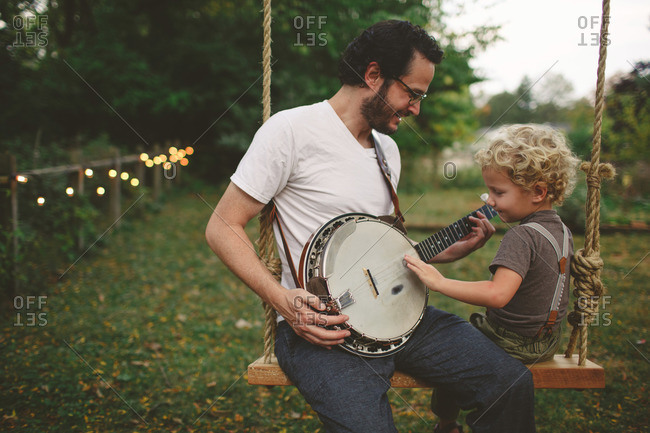 Father showing his son a banjo while sitting on a swing
