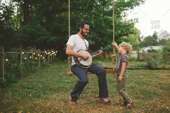 Boy listens to his dad play banjo while on a swing
