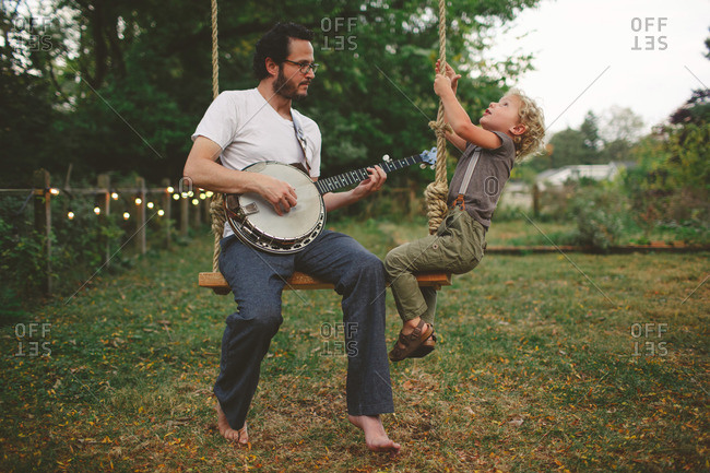 Dad plays banjo while his son climbs on a swing