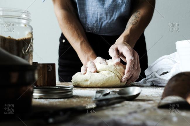 Woman kneading raw dough
