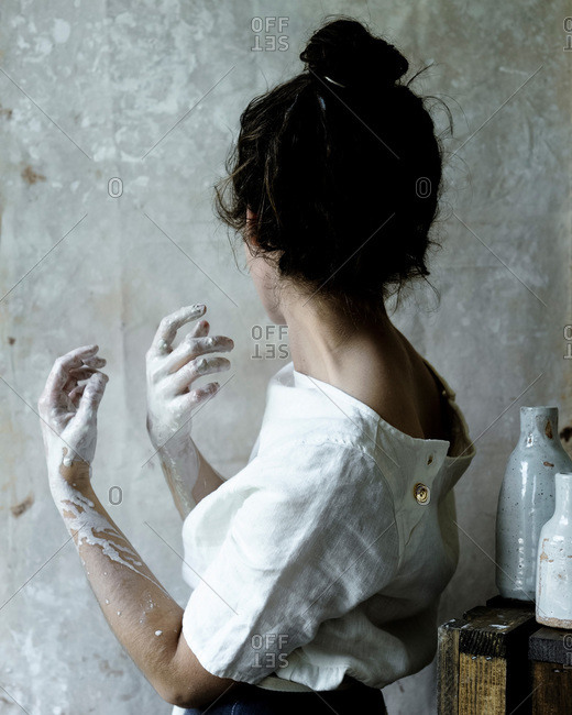 Ceramist with water and clay on her hands