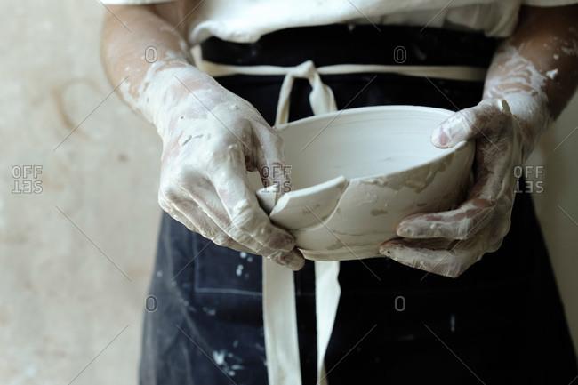 Ceramist holding a broken bowl