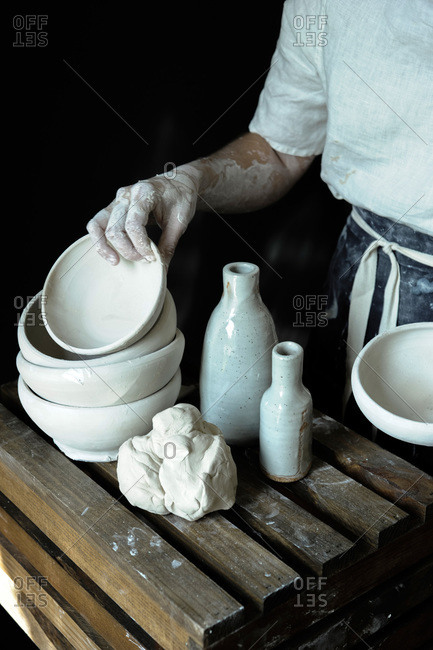 Ceramist with pottery and mound of clay