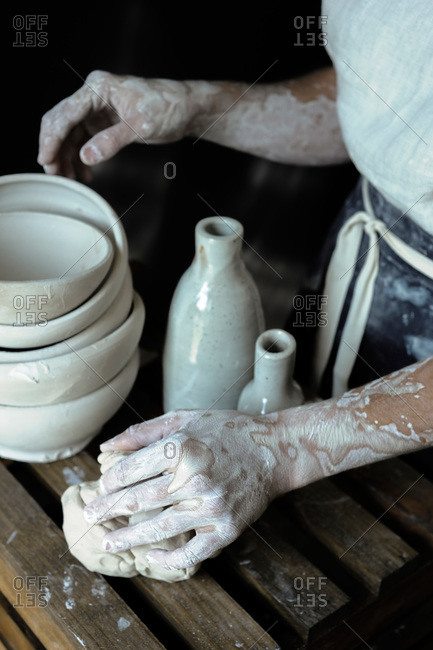 Ceramist with mound of clay and pottery