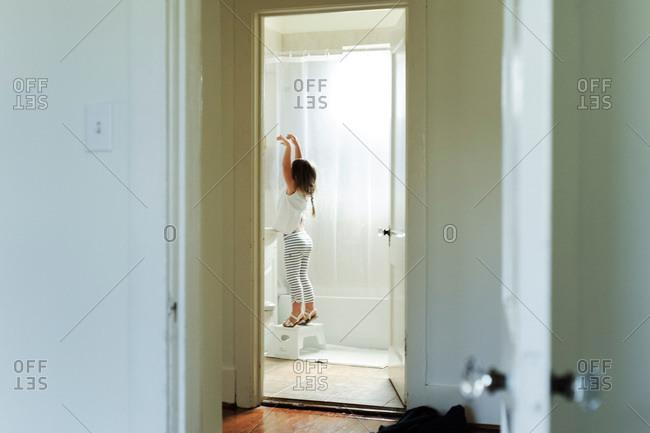 Girl pretending to be ballerina in bathroom mirror