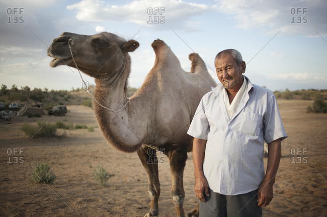 Kyzilkum, Uzbekistan - June 29, 2015: Portrait of camel driver with his camel
