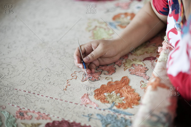 Woman working on an embroidered cloth, Uzbekistan